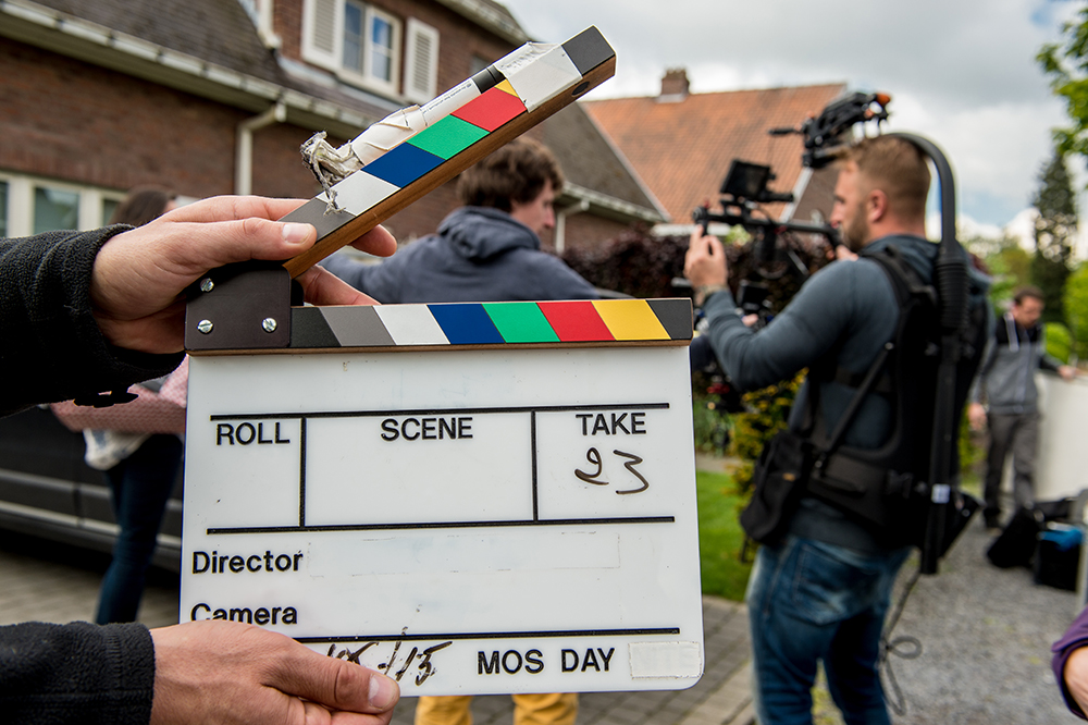 Clapboard for film with crew behind