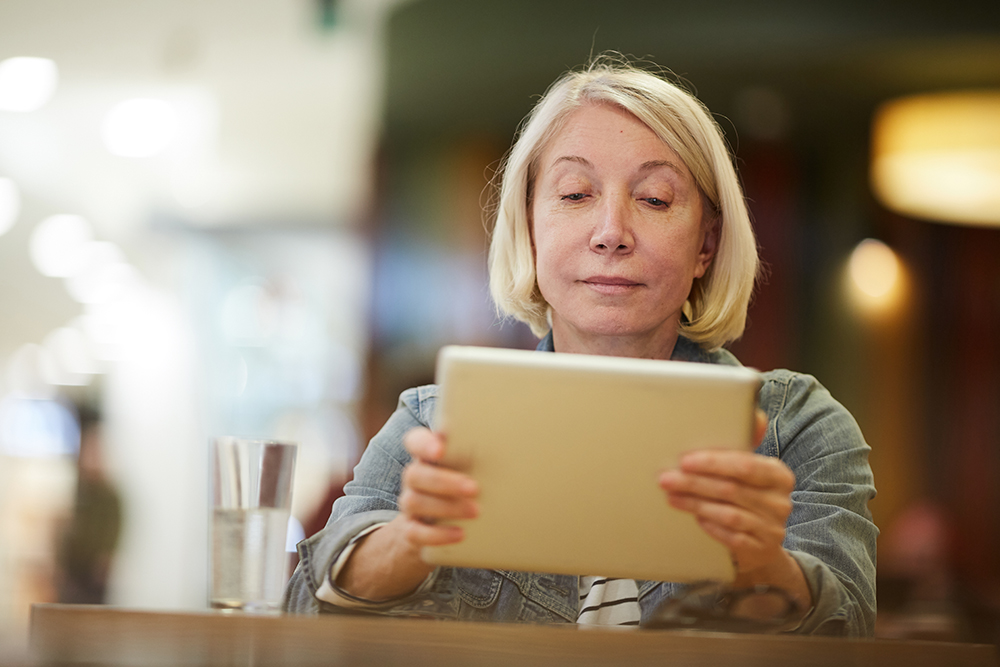 Focussed lady watching medical video on tablet